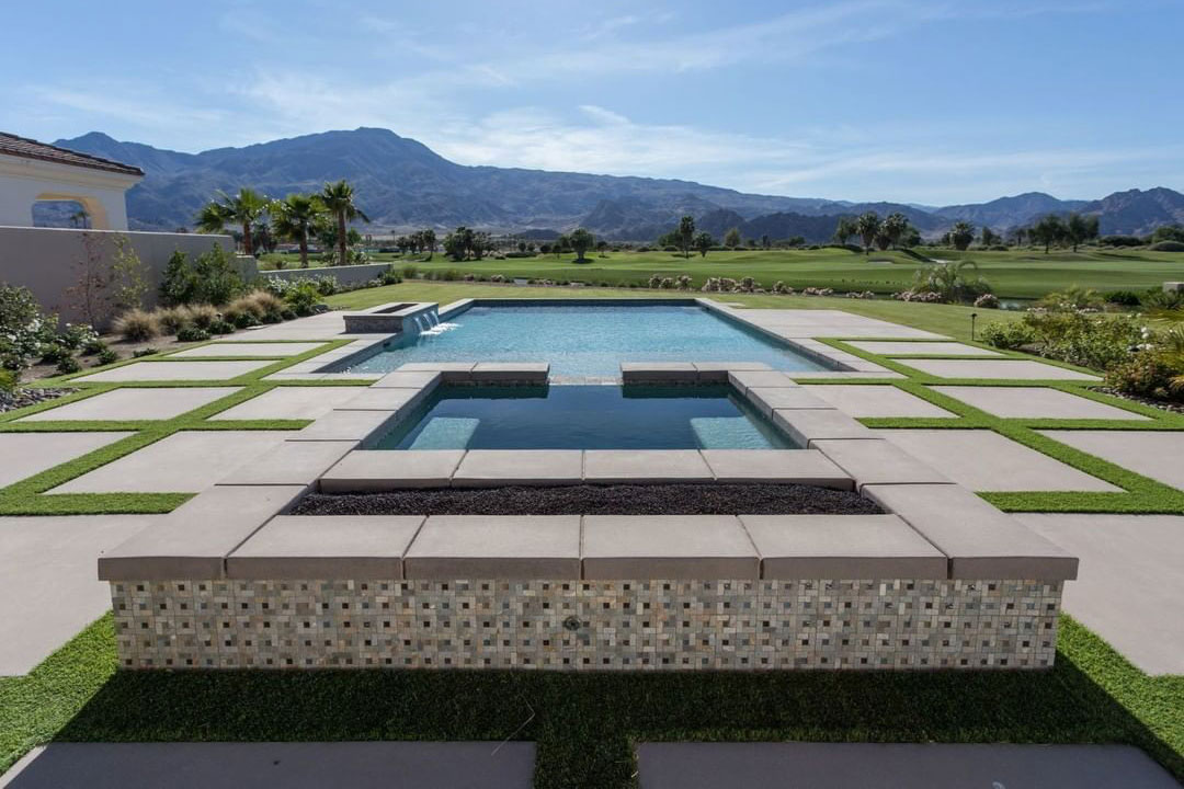 California rectangle pool with raised spillover spa, raised bond beam with scupper trio and fire fea