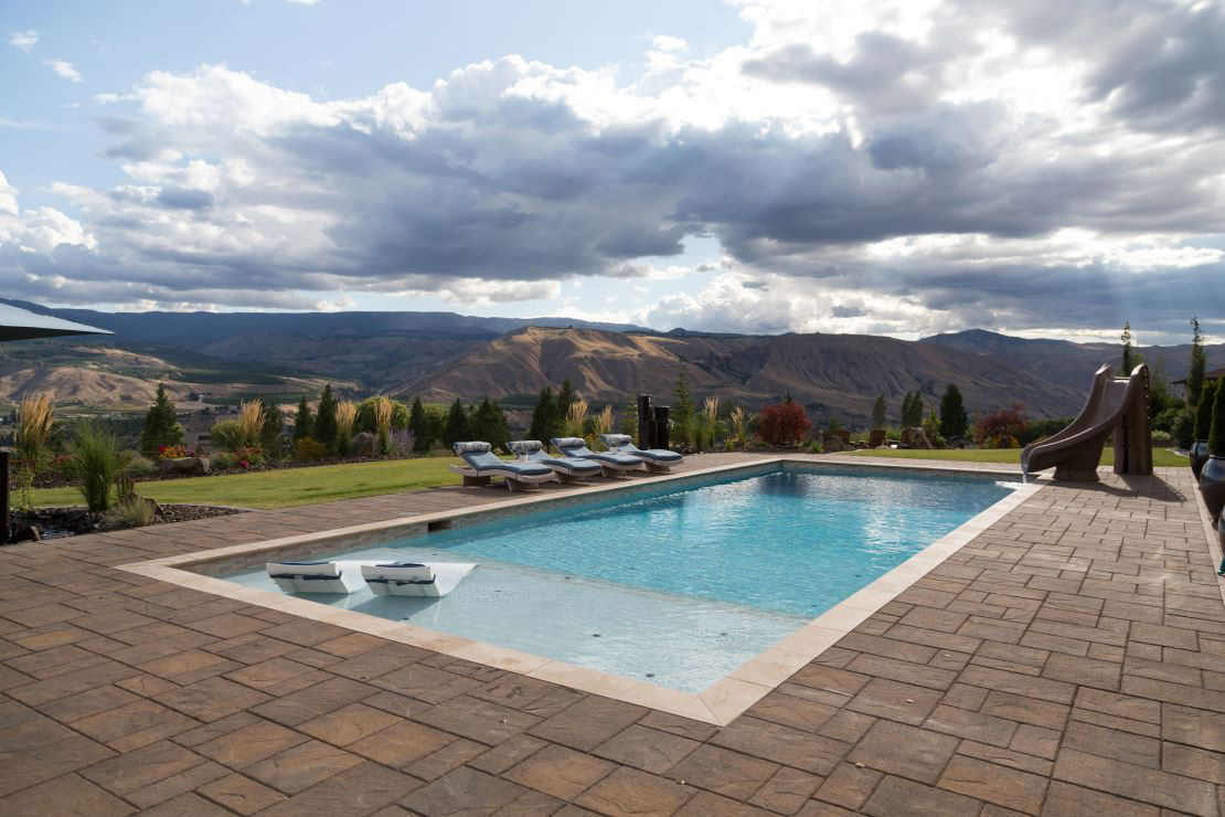 Rectangle pool in the mountains with stamped concrete deck, large tanning ledge, and slide