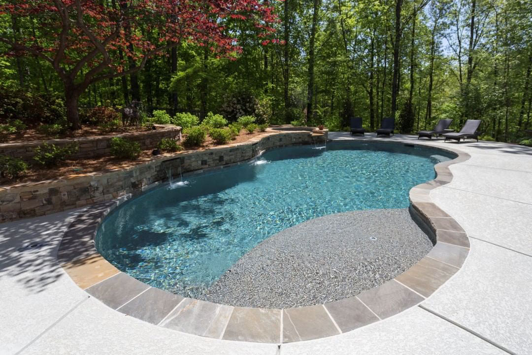 Woodland freeform pool with scuppers mounted in retaining wall, local stone coping, knockdown concre