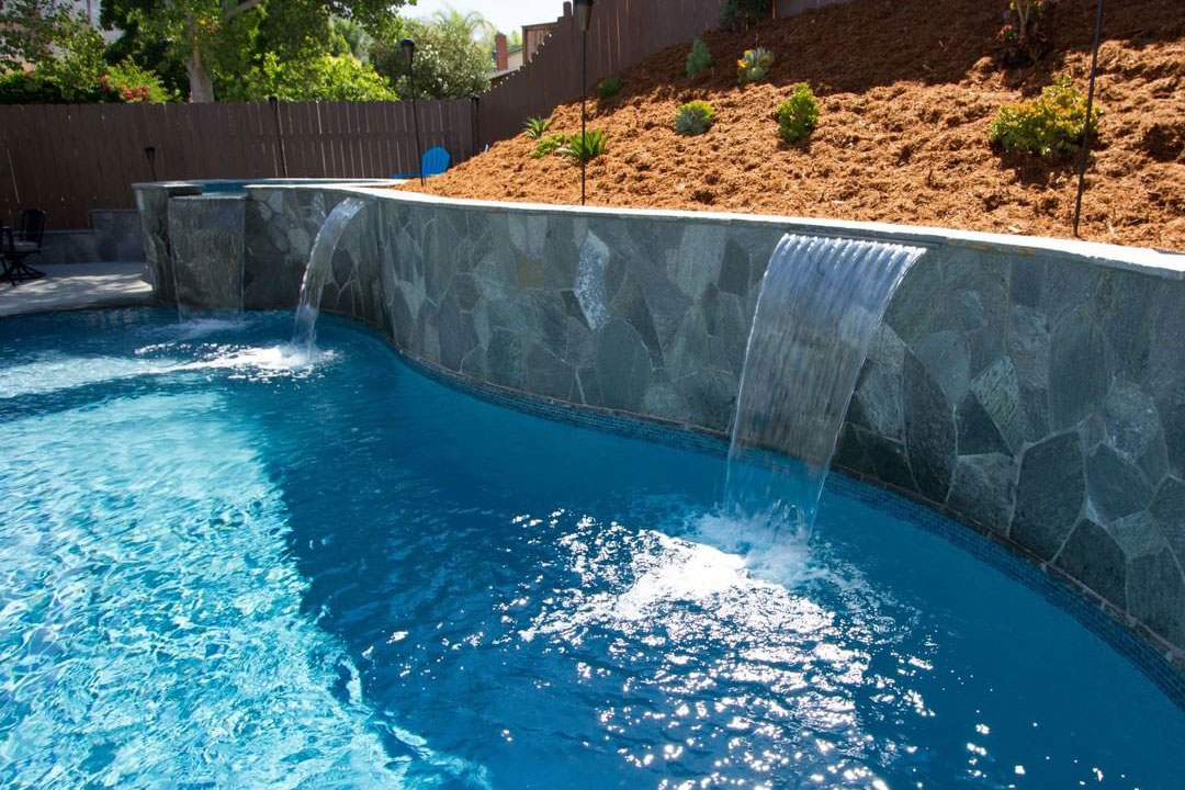 natural stone retaining wall with multiple scuppers and raised spa