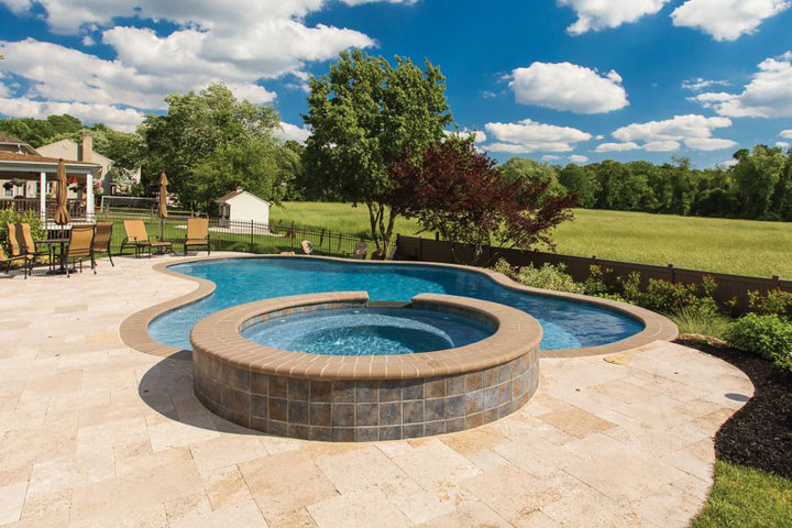 Freeform pool with raised spillover spa and large travertine deck
