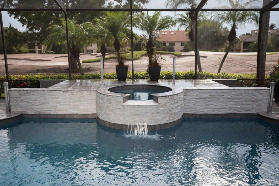 Raised spa and deck section with white stone veneer and grey waterline tile