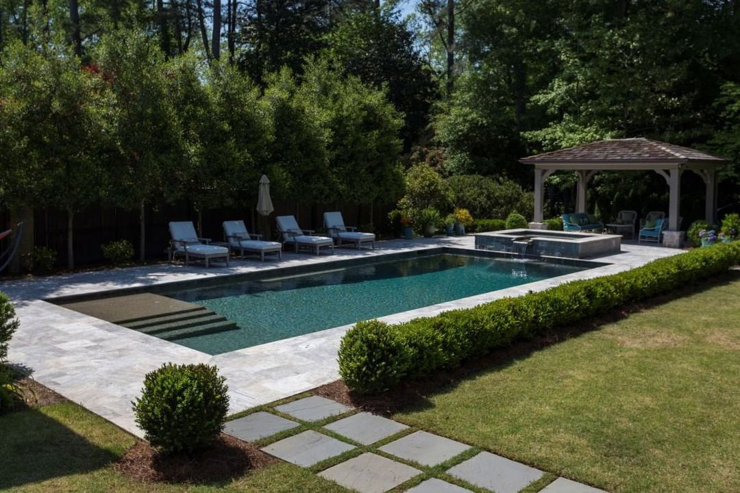 Rectangle pool with corner steps and covered sitting area surounded by travertine deck.