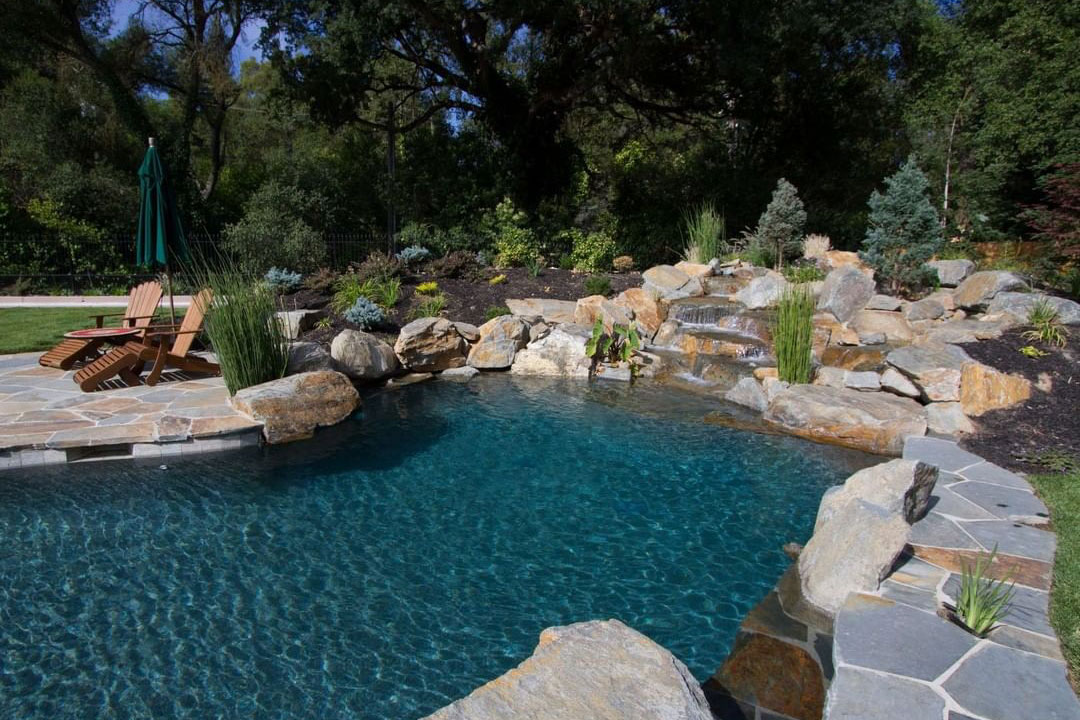 Freeform pool with stony cascade, natural stone decking and coping, and inspired landscaping