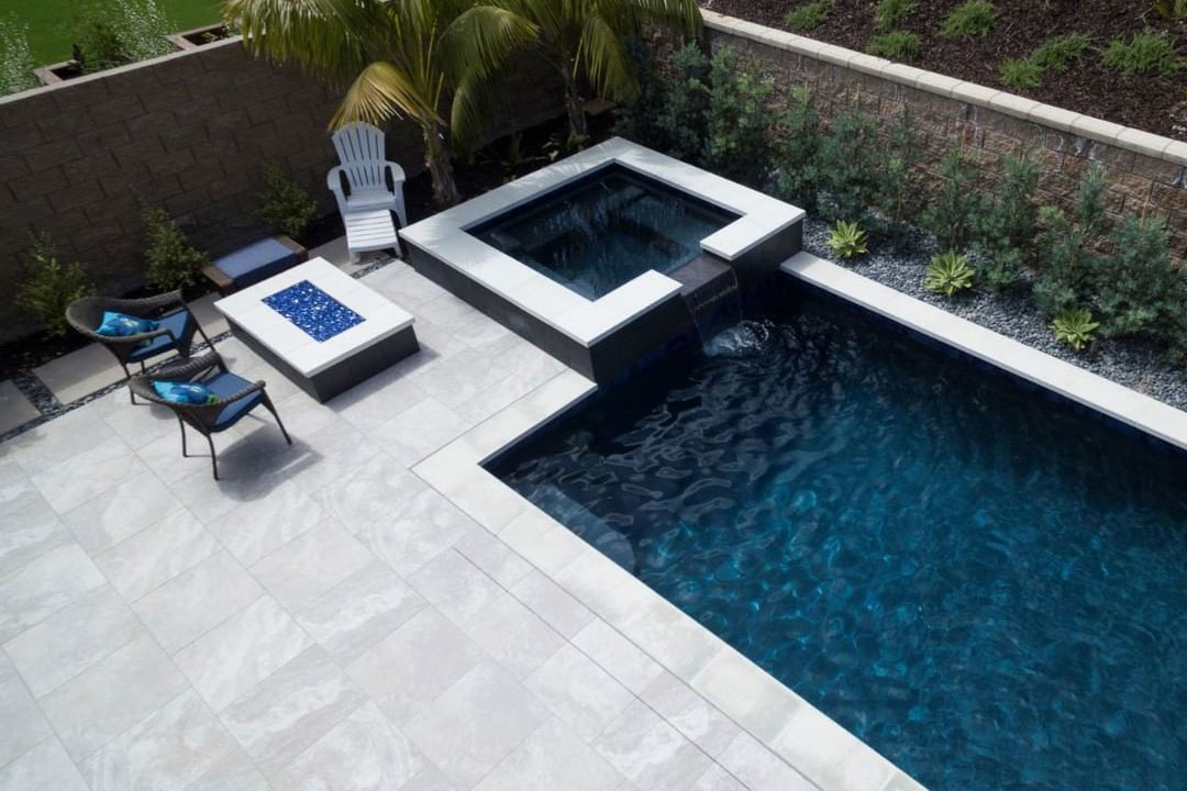 Small, modern rectangle with spillover spa, dark water color, fire pit, and natural stone decking an