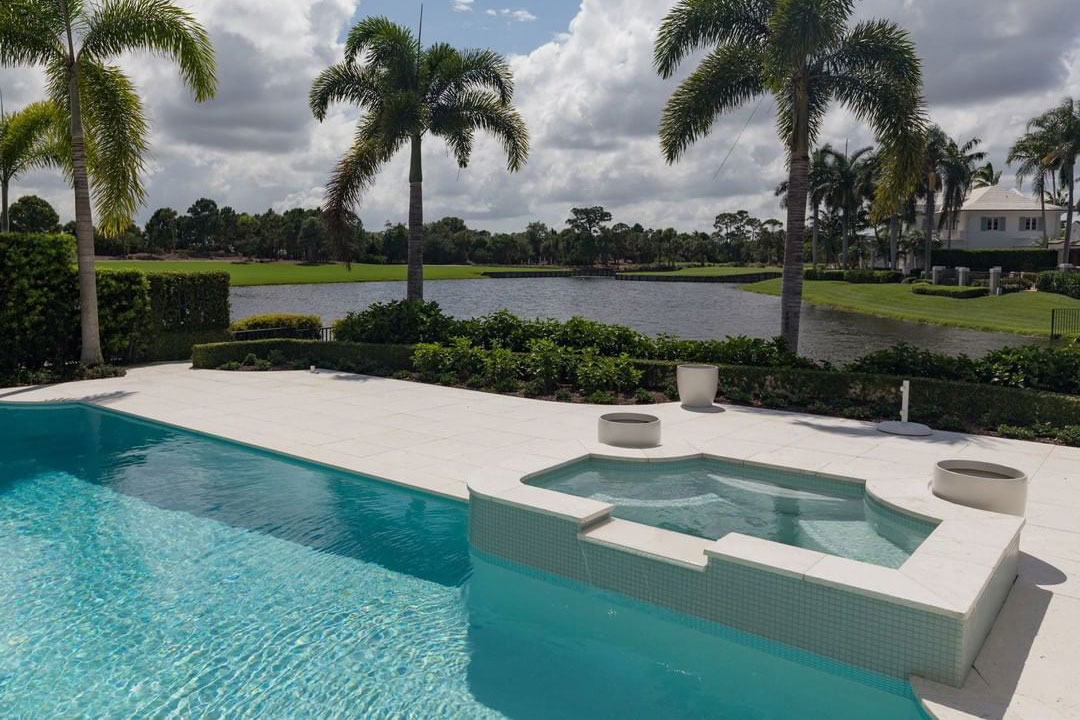 Florida Grecian pool with overflow spa, travertine, and gorgeous lake views.