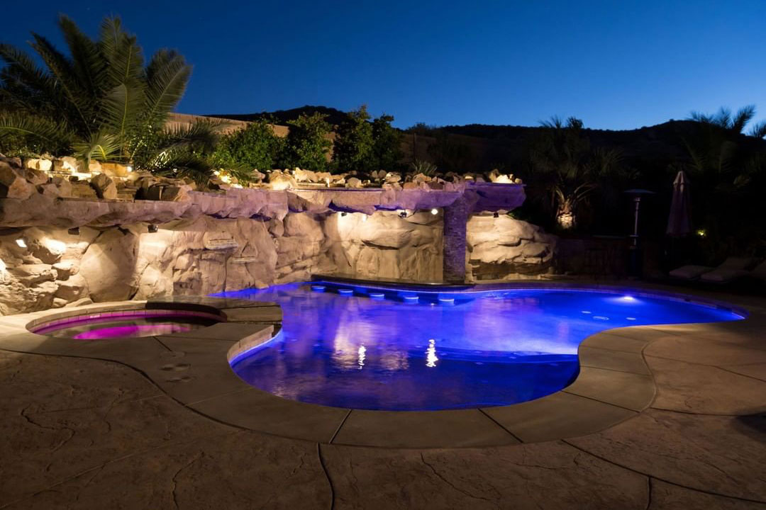California freeform at night with color-changing LEDs, swim-up bar, landscape lighting and concrete