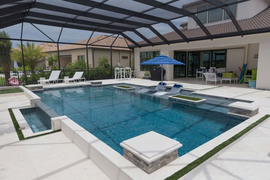 Covered Florida pool with small overflow edge, large tanning ledge with 2 ledge loungers, shade umbr