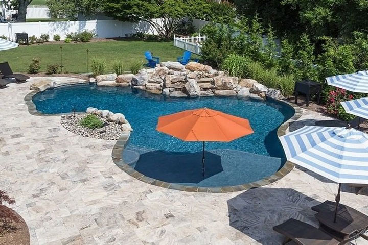 Freeform with large, shaded tanning ledge, and natural stone deck
