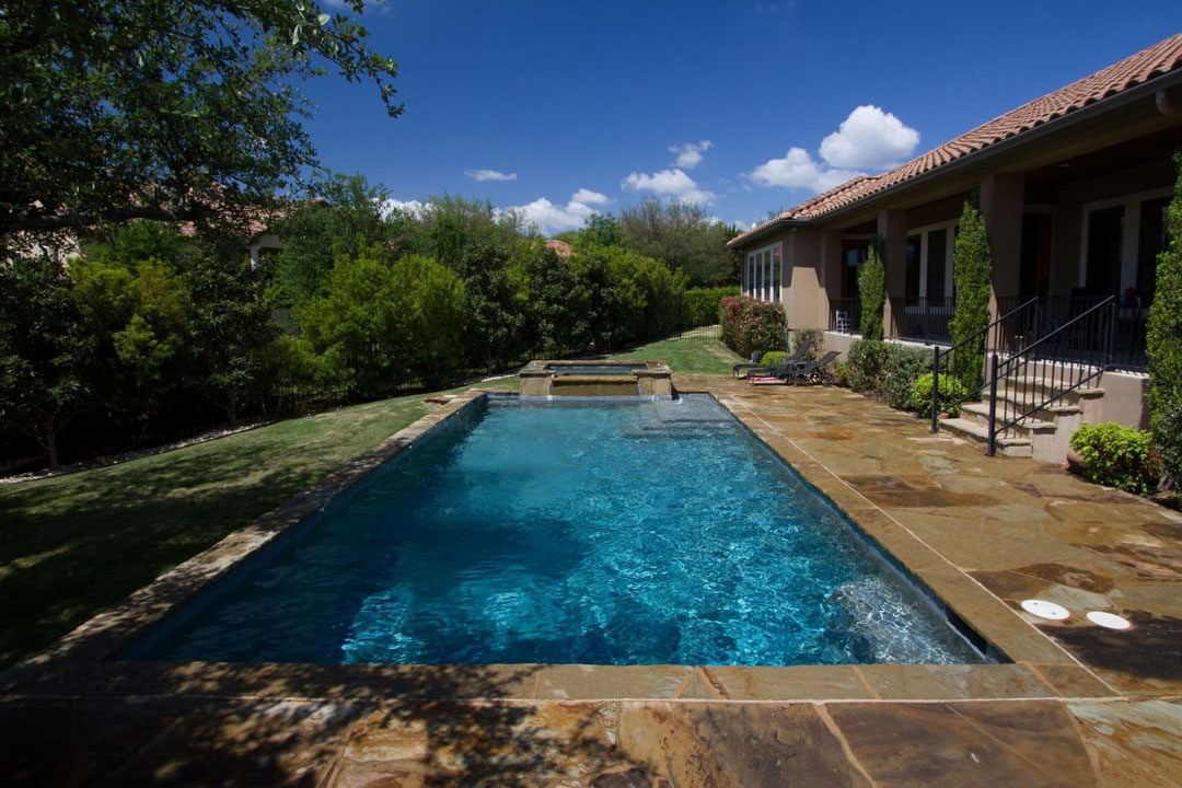 Rectangle pool with overflow spa and natural stone deck
