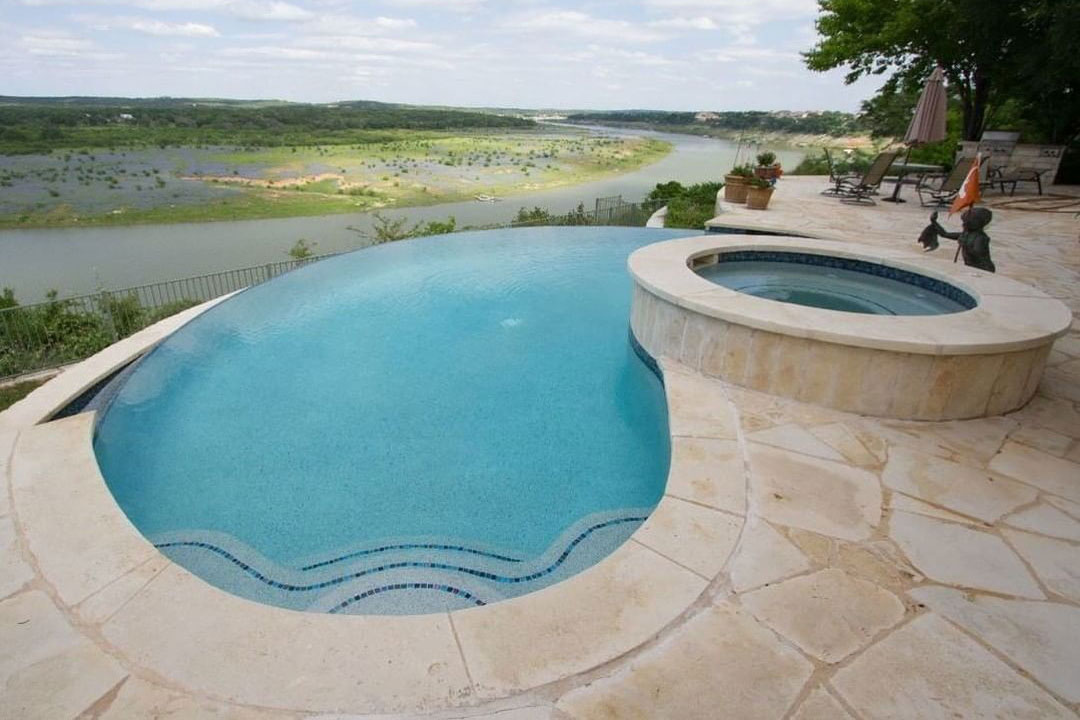 Kidney shaped pool with infinity edge with raised spa overlooking a river