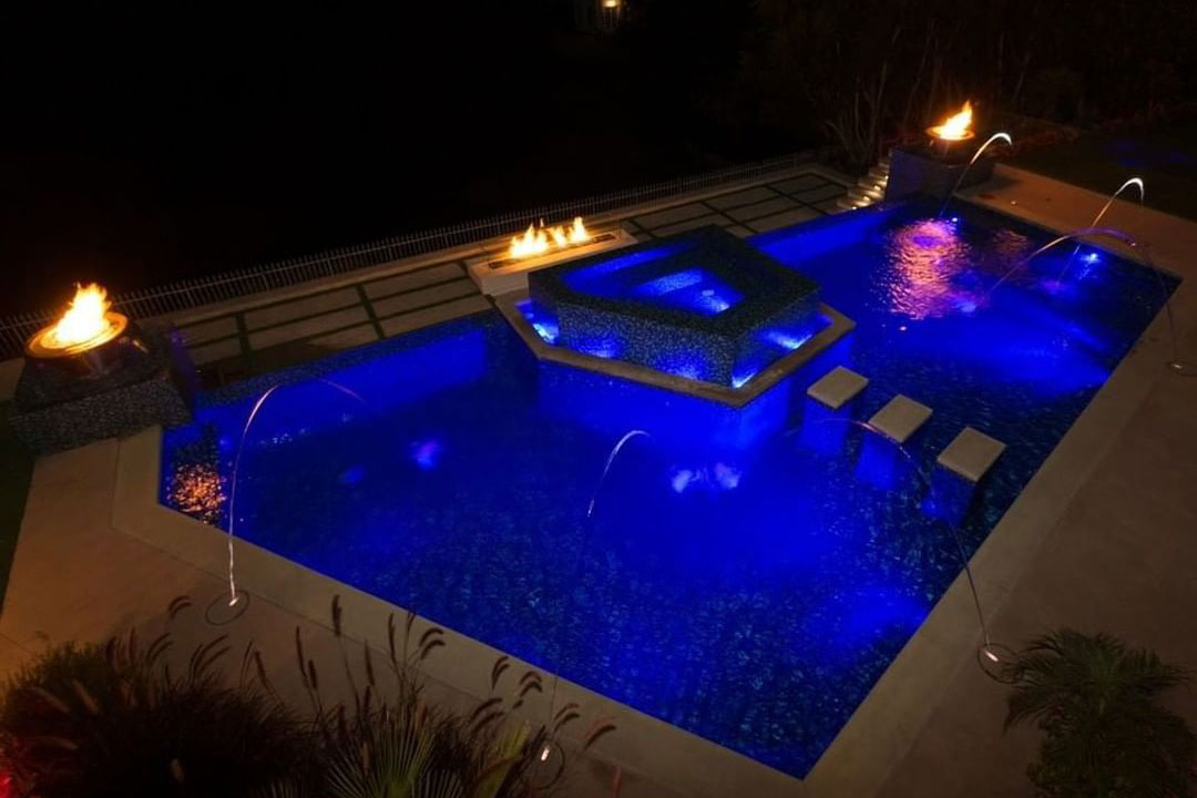 Geometric pool with vanishing edge, laminar jets, fire features, and LED lighting