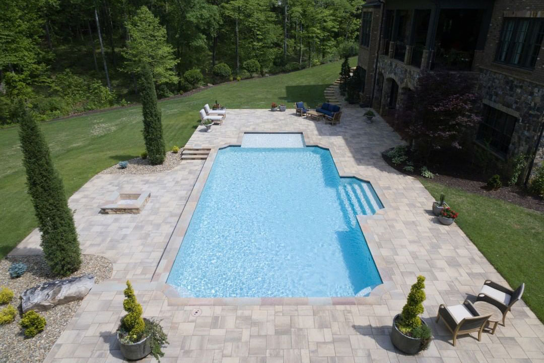 Grecian pool with large tanning ledge, wide steps, and huge deck with fire pit