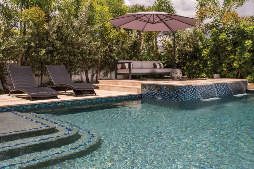 Geometric pool with raised travertine deck, glass tile, large shade umbrella and loungers