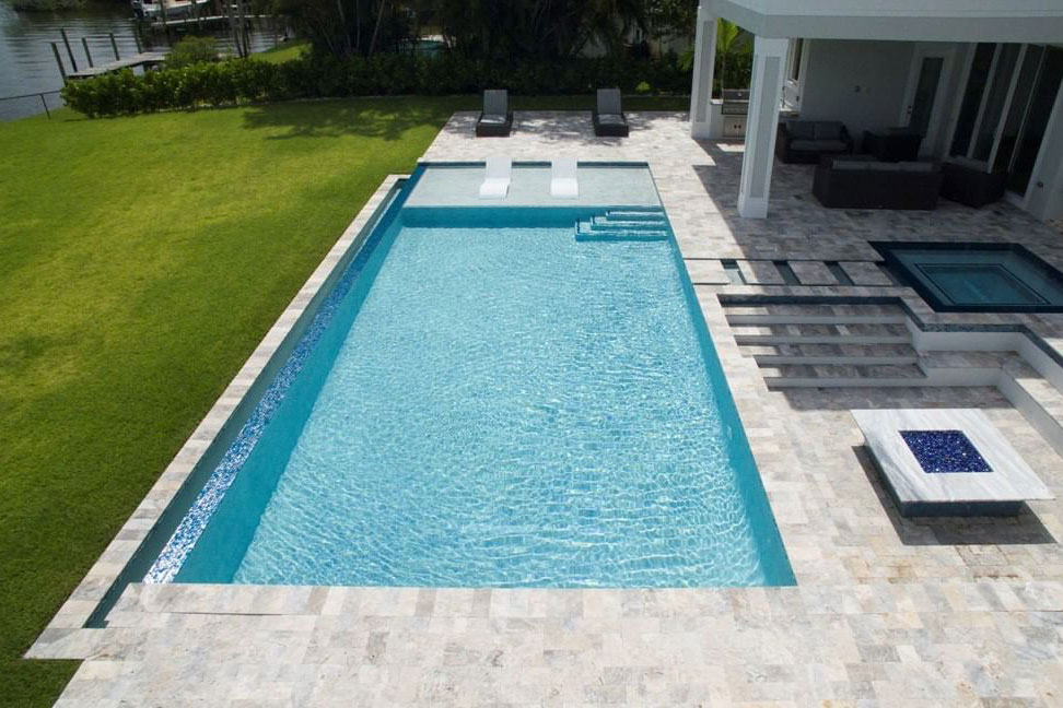 Rectangle pool with large tanning ledge, fire pit area, inground spa, and infinity edge