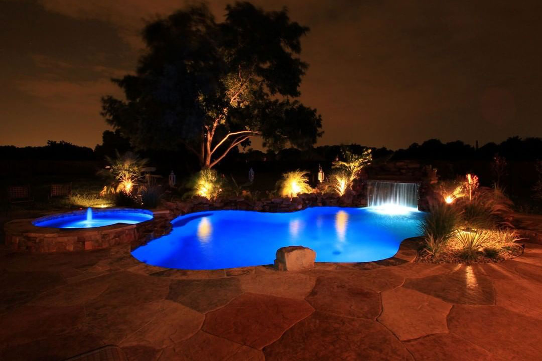 Freeform at night with Pentair Intelliconnect LED system, waterfall grotto, and landscape lighting
