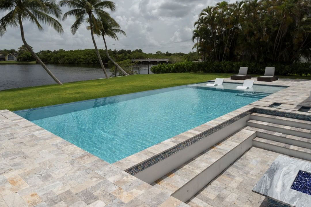 Vanishing edge rectangle pool with tanning ledge, in-pool loungers, sunken fire pit area, and river