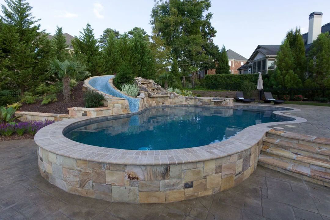 Freeform pool with all-tile slide, clay coping, natural stone elements, and stony cascade
