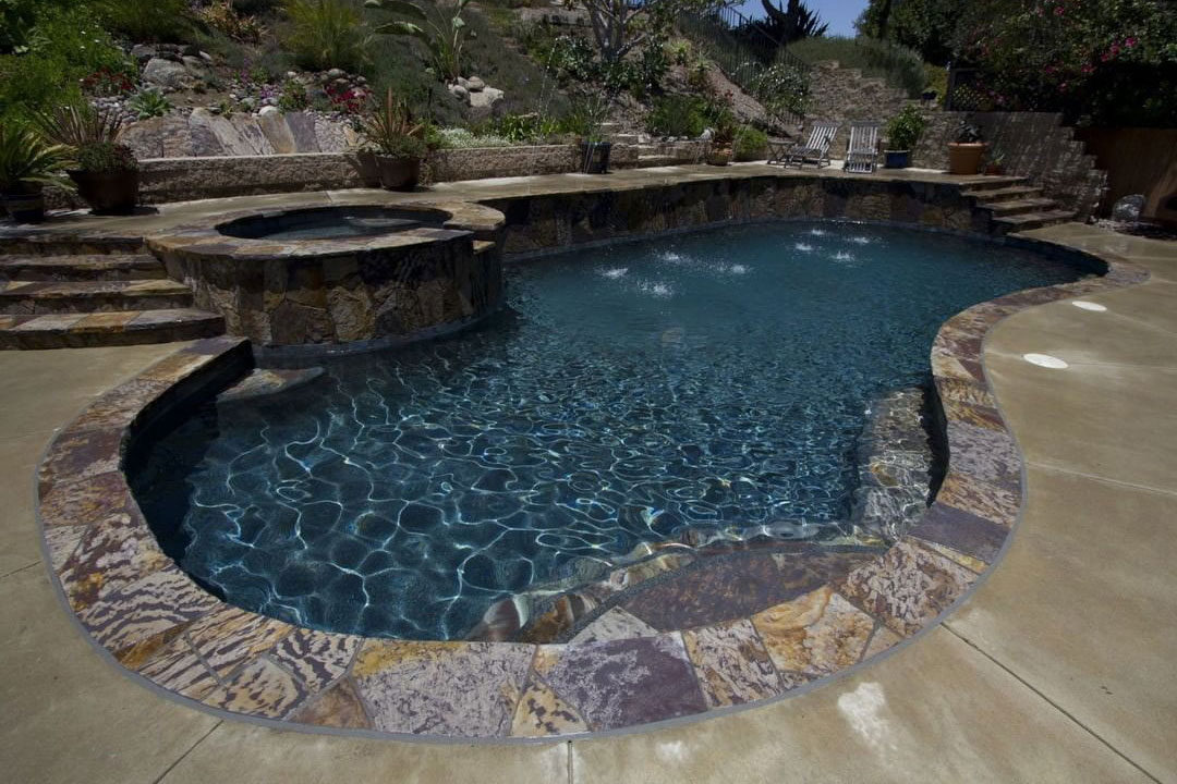 Kidney shaped pool with natural stone coping and raised deck and spa