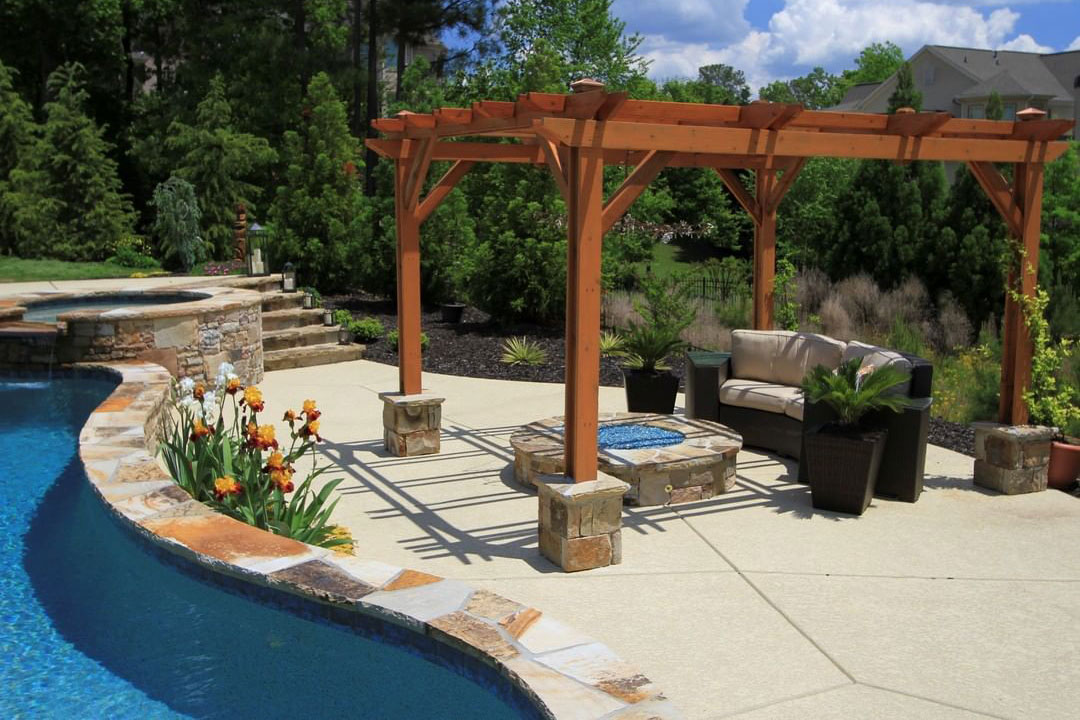 Firepit sitting area with pergola next to freeform with overflow spa, natural stone coping and blue