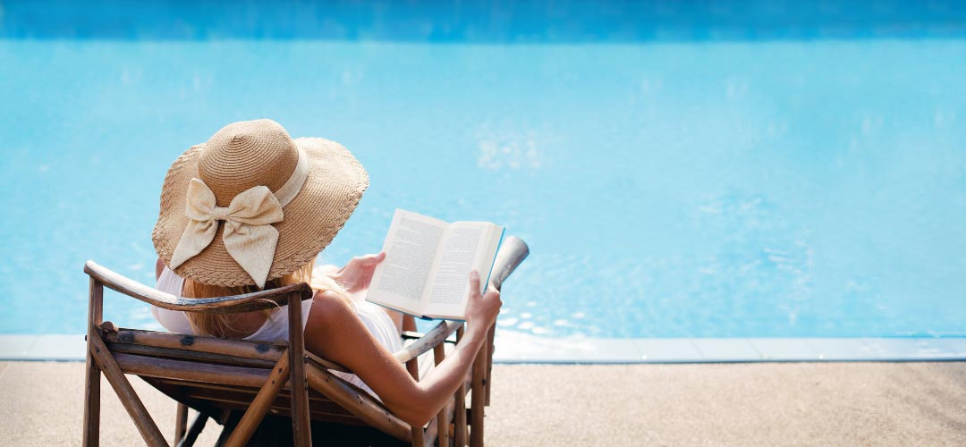 Woman Reading Book, While Lounging at the PoolPoolside