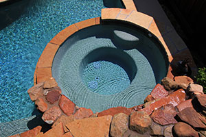 Rustic – Clay Colored Circular Spa, Rocky Wall