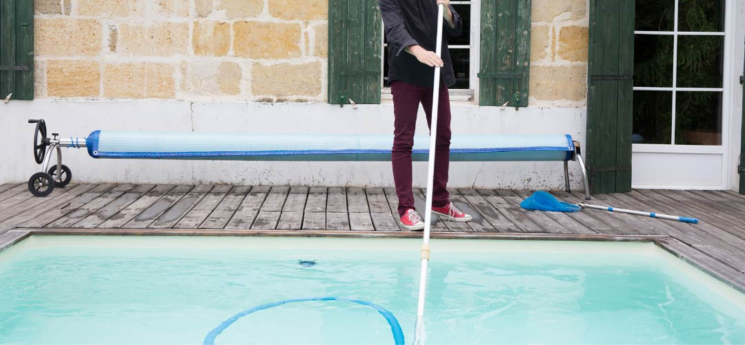 Man Vacuuming Swimming Pool