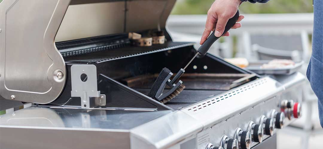 man cleaning outdoor grill